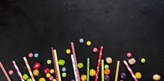 Paglia del cocktail e mini caramella su un fondo nero, vista superiore, Fotografia Stock Libera da Diritti
