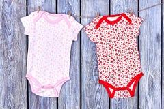 Pagliaccetti della neonata che appendono sulla corda Fotografie Stock