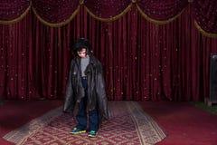 Pagliaccio d'uso Make Up del ragazzo e grande cappotto in scena Fotografia Stock