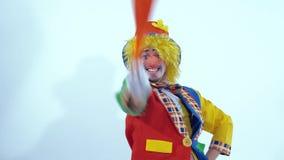 Pagliaccio di circo ballante e sorridente che gira intorno e che ondeggia un panno arancio stock footage