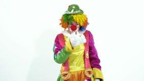Pagliaccio di circo variopinto in cappello verde che gioca con lo scheletro del giocattolo-pesce video d archivio