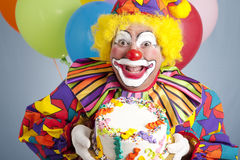 Pagliaccio di compleanno con la torta in bianco Immagine Stock