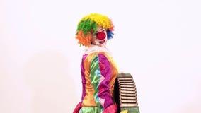 Pagliaccio divertente in modo divertente che gioca l'armonica, il canto ed il dancing allo stesso tempo video d archivio