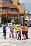 Pagliaccio e bambini sulla via Fotografia Stock