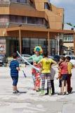 Pagliaccio e bambini sulla via Immagini Stock