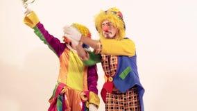 Pagliaccio femminile divertente che prende in giro il pagliaccio di circo maschio non dandogli la giocattolo-carota video d archivio