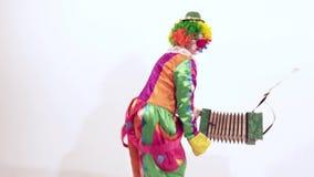 Pagliaccio femminile divertente divertendosi mentre ballando attivamente tenendo armonica video d archivio