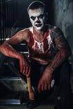Pagliaccio-maniaco sanguinoso con l'ascia Immagini Stock