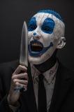 Pagliaccio terribile e tema di Halloween: Pagliaccio blu pazzo in un vestito nero con un coltello in sua mano isolata su un fondo Fotografia Stock