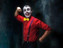 Pagliaccio terribile e tema di Halloween: Pagliaccio rosso pazzo in una camicia con le bretelle immagine stock libera da diritti