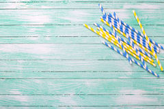 Paglie di carta blu e gialle luminose sul backgrou di legno del turchese Fotografia Stock