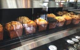 Pagnotta del muffin e cioccolato del muffin nel dispositivo di raffreddamento del dolce sul caffè, immagine stock libera da diritti