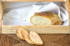 Pagnotta del pane bianco affettato dell'artigiano, sulla tavola nei breadbas immagini stock libere da diritti