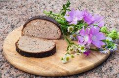 Pagnotta del pane di segale con i semi di cumino ed i fiori selvaggi Fotografia Stock