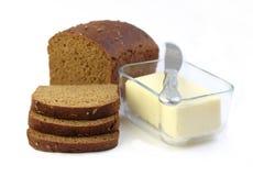 Pagnotta del pane di segale con le fette e del burro in un contenitore di vetro Fotografie Stock Libere da Diritti