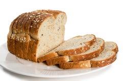 Pagnotta di pane affettato sulla zolla. Fotografia Stock