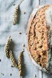 Pagnotta di pane e delle orecchie rustici freschi di grano sulla cucina Fotografia Stock