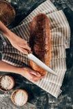 pagnotta di taglio della donna su tela sul ripiano del tavolo scuro con farina Fotografie Stock