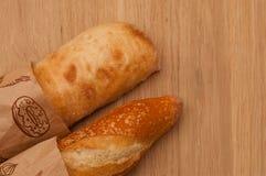 Pagnotta francese e ciabatta italiana su un bordo di legno Fotografia Stock