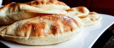 Pagnotte della pita, pane piano arabo che è mangiato solitamente con le salse e le immersioni quali i hummus e il labneh fotografia stock