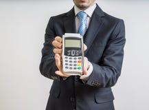 Pago con de la tarjeta de crédito El hombre de negocios lleva a cabo el terminal del pago disponible Imagenes de archivo