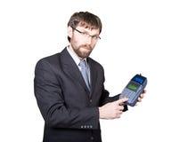Pago con la tarjeta de crédito - hombre de negocios que lleva a cabo la posición terminal En el fondo blanco Imagen de archivo