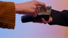 Pago con la tarjeta de crédito de la raya magnética a través del terminal, aislado en fondo azul y amarillo existencias Cierre pa almacen de metraje de vídeo