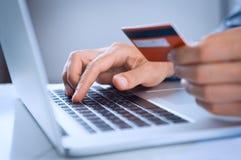 Pago del hombre en línea con la tarjeta de crédito Imágenes de archivo libres de regalías