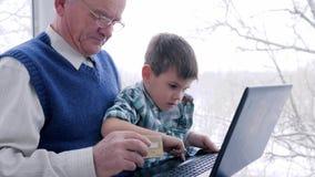 Pago en línea, abuelo con la tarjeta de crédito en manos y nietos para hacer compras en Internet vía el ordenador almacen de video