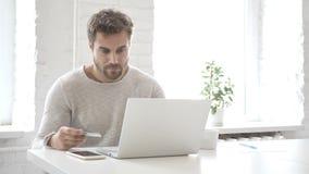 Pago en línea con la tarjeta de débito del hombre en el ordenador portátil almacen de video
