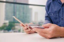 Pago en línea, manos del hombre joven del primer que sostienen una tarjeta de crédito y que usan el teléfono elegante para las imágenes de archivo libres de regalías