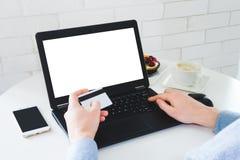 Pago en línea usando el cuaderno y la mofa de la tarjeta de crédito para arriba foto de archivo libre de regalías