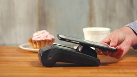Pago móvil con tecnología de NFC en café metrajes