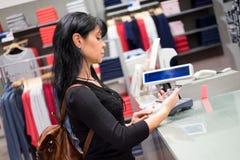 Pago móvil La muchacha paga hacer compras usando el teléfono móvil Imagen de archivo