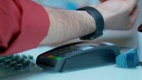Pago sin contacto con el smartwatch El pagar drogas con tecnología del nfc almacen de metraje de vídeo
