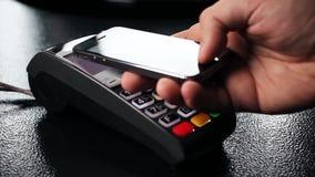 Pago sin contacto con su smartphone El pagar con un dispositivo del smartphone en un terminal de la tarjeta de crédito Pago inalá metrajes
