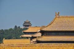 Pagod på en kulle med traditionella kinesiska tak i förgrund arkivbild