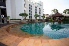 Pagoda, barra en la piscina, ociosos del sol al lado del jardín y edificios Foto de archivo libre de regalías