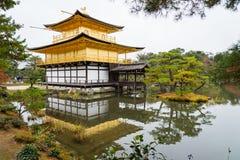 Pagoda dorata con l'albero verde e riflessione sul lago in autunno a immagine stock