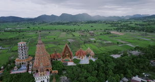 The pagoda, golden buddha statue with rice fields and mountain background, Wat Tham Sua stock footage