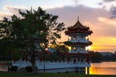 Pagoda hermosa por el agua durante puesta del sol Fotografía de archivo libre de regalías