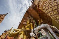 Pagoda ottagonale e grande statua dorata di Buddha al tempio della caverna di Wat Tham SuaTiger, distretto di Tha Muang, Kanchana immagine stock