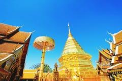 Pagoda, paraguas y estatua de oro grandes de Buda con el backgound claro del cielo azul en el wat Phra que Doi Suthep Chiangmai,  fotografía de archivo libre de regalías