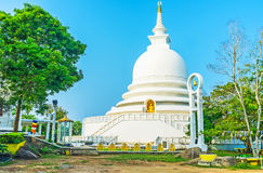 Pagoda on Rumassala mount. The white Japanese Peace Pagoda Sama Ceitya surrounded by lush greenery of garden on Rumassala mount, Unawatuna, Sri Lanka stock photography