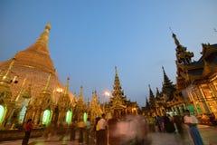 Pagoda serrée de Shwedagon complètement des touristes et des passionnés locaux le soir pendant le coucher du soleil Photos stock