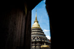 The Pagoda. The view of the landmark Pagoda in Lampang provice of Thailand framed by the wooden door Royalty Free Stock Photo
