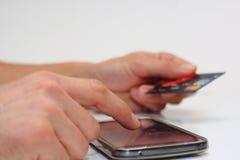 Pagos que entran en línea usando un teléfono móvil y una tarjeta de crédito Fotos de archivo