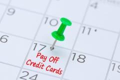 Pague fora os cartões de crédito escritos em um calendário com um pino verde do impulso foto de stock royalty free