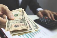 Pague o dólar americano, dinheiro do dólar do uso da mão na mesa de escritório dentro Fotos de Stock Royalty Free