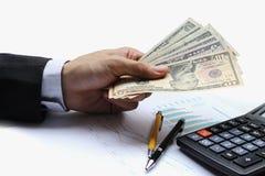 Pague o dólar americano, dinheiro do dólar do uso da mão na mesa de escritório dentro Imagem de Stock